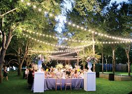outdoor backyard unique wedding decorations with string lights and large table also wooden chairs plus wedding flowers