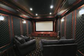home theater room with recessed ceiling can lights and wall sconces