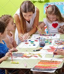Nursery Teacher Nursery Teacher Painting With Children In Kindergarten Photos By Canva