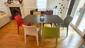 modern dark wood extending dining table and colourful faux leather dining chairs