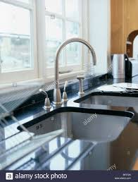 Kitchen Worktop Granite Close Up Of Stainless Steel Tap And Under Set Sink In Black