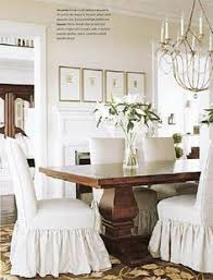 white slipcovered chairs and rustic table dining