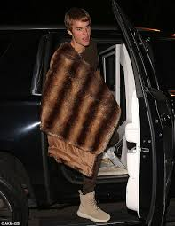 here he comes justin bieber carried a heavy fur coat over one shoulder as he