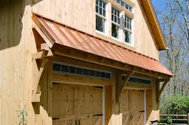 timber frame eyebrow roof with copper standing seam on carriage barn over garage doors