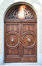 Large arched wooden front door design with intricate carving detail