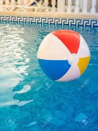 beach ball in pool. Beach Ball In Blue Pool Water. Sunlight Ripples The Small Waves. Stock Photo