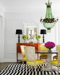 a graphic rug lends lightens the load of a heavy pedestal table paired with french chairs upholstered in yellow leather and backed with faux crocodile