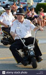 shriner riding a mini motorcycle in a parade demonstration stock