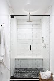 white shower walls with black hex shower floor tiles