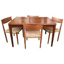 danish modern extendable teak dining table with woven chairs from a unique collection of antique and modern dining room sets at