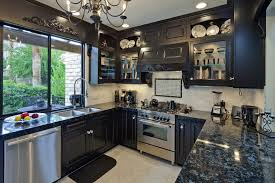 busy kitchen with a country style that has black cabinets and dark gray granite countertops