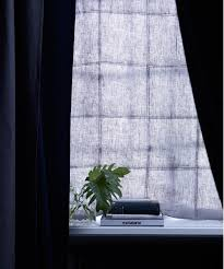 a dark blue soundproofed curtain hanging at the window blocks out outdoor noise as well