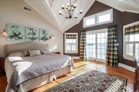 Cottage Master Bedroom with Cathedral ceiling, Chandelier, Carpet, Wall  sconce, Exposed beam