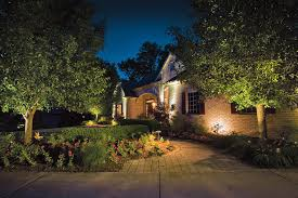 simple and easy home landscape lighting on front yard of beautiful house with wall bricks planted with 2 large trees and various kind of ornamental flowers