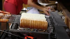 Kurtoskalacs or traditional romanian chimney cake cooking over burning  embers Stock Video Footage - VideoBlocks