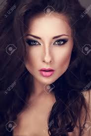 beautiful woman with bright y makeup eyes and pink lipstick looking y closeup toned portrait