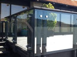 glass panels between wood posts with a stainless steel standoff