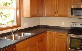 traditional kitchen remodel with black laminate countertops maple wood finish cabinets and double basin stainless steel sinks