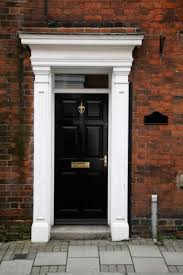 black exterior door with white columns and entablature