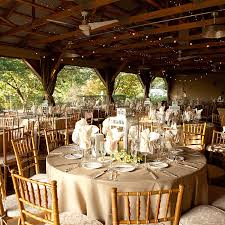 rustic country wedding reception decorations with exposed beam ceiling and glass lanterns on round tables also wooden chairs
