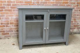 furniture grey wooden tv cabinet with swing glass door and two shelf combined brick wall white