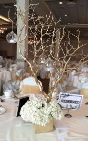 Arrangement includes gold sprayed manzanita branches, hydrangeas, gold  square vase and