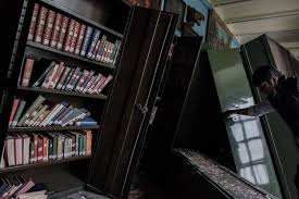 an employee looks at damaged book shelves at the kaiser library in kathmandu on may 7