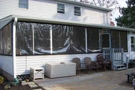 these winter drop panels were placed over an existing screened in porch to create this clear plastic enclosure plastic patio panels