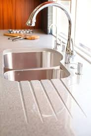 kitchen sink with drainer board drain board built into a granite counter top in a white