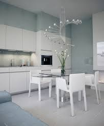 spiral kitchen chandelier design over glass top dining table and 4 white armchairs in contemporary white kitchen