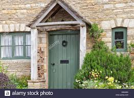English old stone cottage with green doors, wooden entrance canopy ...