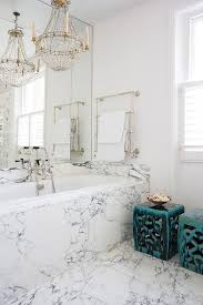 chic bathroom a paris flea market chandelier and a wall mount towel warmer placed over a marble clad bathtub next to blue stools
