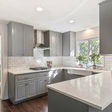 Gray shaker cabinets, white quartz counter tops, Grecian white marble  subway tile and a farmhouse sink are sure to outlast moods and trends!