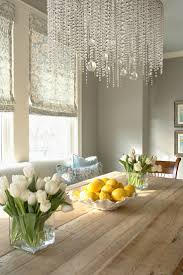 crystal linear chandelier with glass window and wall art plus wood table also flowers and orange fruits plus white sofa for luxury dining room design ideas