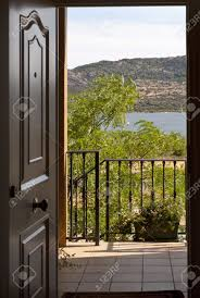 can see the open door of a home with a balcony and a lake in the