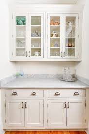 butlers pantry built with painted white inset shaker cabinets white marble countertops and stacked crown