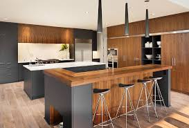 modern kitchen with gray cabinets and wood countertops with cone shaped pendant lighting