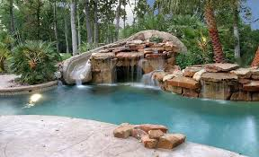 tropical swimming pool with rock water feature waterfall
