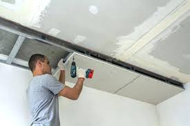fixing ceiling drywall construction worker assemble a suspended ceiling with drywall and fixing the drywall to fixing ceiling drywall