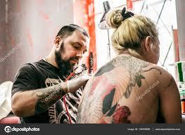 процесс создания тату на спине девушка стоковое фото Lakschmi