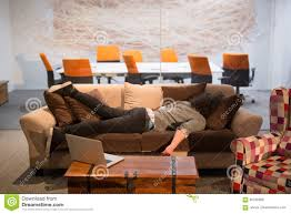 a young cal businessman sleeping on a sofa during a work break in a creative office