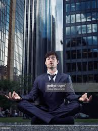 meditation businessman office. conceptual portrait of a businessman wearing suit sitting crosslegged meditating outdoors with downtown office buildings meditation o