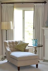 master bedroom chaise in front of bay window home
