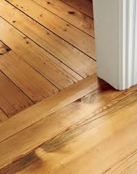 reclaimed antique hemlock flooring used in the new addition meets the original floors shown at top