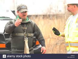 Diver Dustin Arnold (L) gets last minute instructions from a Metropolitian  Sewer District employee before entering a sewer manhole to install a large  plug into an inlet to prevent flooding from the