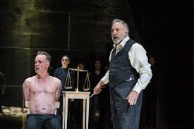 key moments the merchant of venice royal shakespeare company antonio jamie ballard sitting half naked in a chair is menaced by
