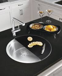 chrome faucet and round drop in kitchen sink with cutting board by kohler