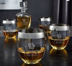 four whiskey glasses with silver rims and a whiskey decanter all engraved