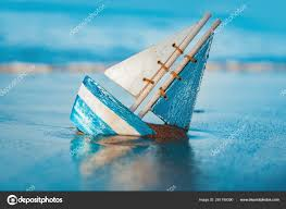 wooden toy sailboat buried into sand near the seas in summer vacation and leisure concept concept Фото автора micrologia