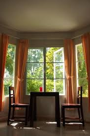 simple bay window curtain rods with orange curtain and shabby chic chairs